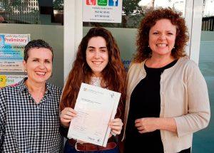 Frente de su academia de inglés alumna Irene con su madre y Miss Clare recibiendo su certificado después de haber aprobado el examen de inglés de Cambridge nivel B2